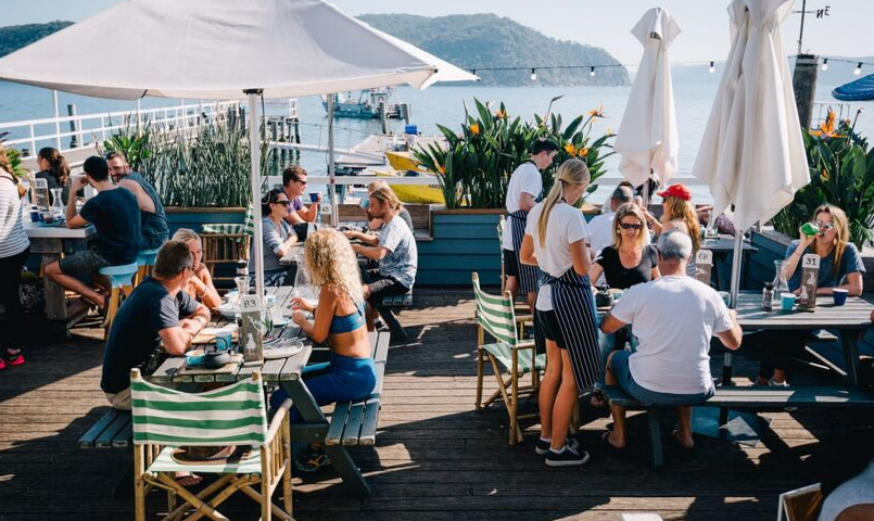 The outdoor deck at the Boathouse at Palm Beach on a busy sunny day with all tables full and a waitress taking someone's order