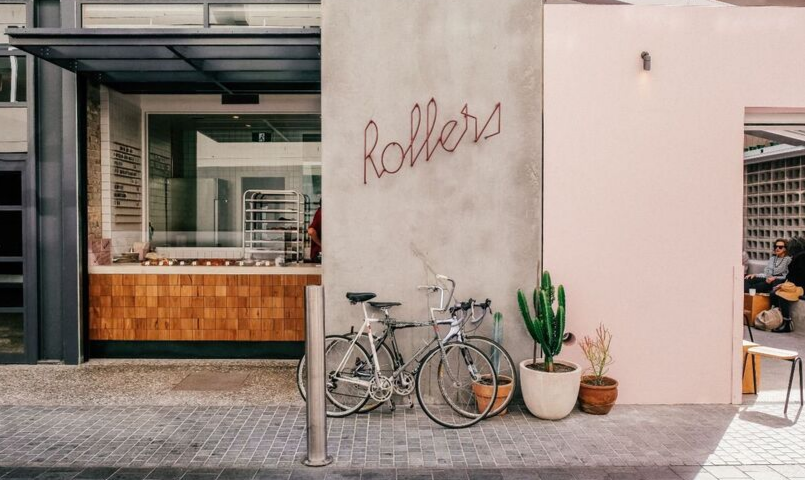 Exterior shot of the pink Rollers Bakehouse cafe in Manly with vintage bikes parked out the front