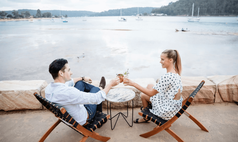 Couple cheers with their drinks at The BOX on the Water at Ettalong Beach