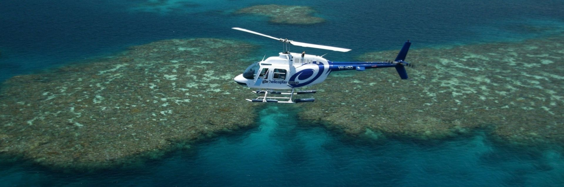 Helicopter hovering over the iconic aqua blue and green scene of the Great Barrier Reef