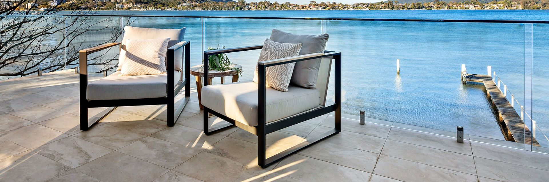 Belle Property Escapes property balcony featuring two sitting chairs overlooking the water at Point Clare