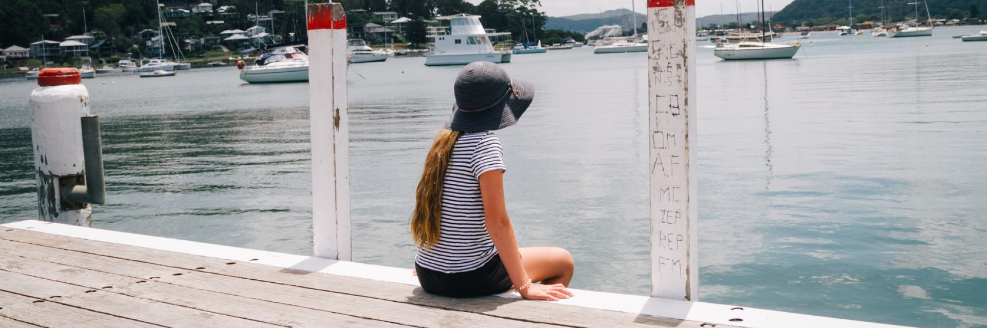 Girl sitting on the wharf overlooking the water at Killcare