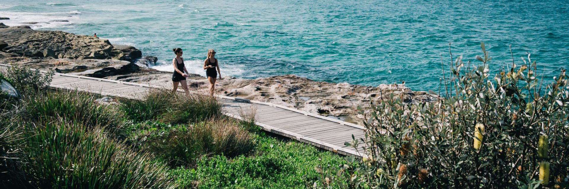 Two girls walking on the coastal track near Curl Curl in the Northern Beaches of NSW